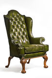 Antique green leather wing chair carved legs isolated Royalty Free Stock Image