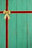 Antique green old wood door with red and gold velvet Christmas ribbon and gold bow border Stock Image