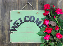 Antique green welcome sign with flower border of red roses hanging on rustic wood background Stock Photo
