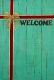 Antique green welcome sign with red and gold velvet ribbon Christmas background Stock Photos