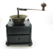 Antique Grinder. This is a photo of an antique coffee grinder against a white background. It is a very heavy cast iron construction with a wooden crank handle stock image