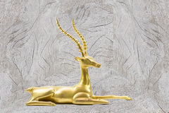 Antique grunge brass deer sculpture on wooden background Royalty Free Stock Photography
