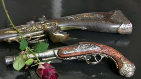 Antique guns and withered roses stock video footage