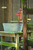 Antique Hand Water Pump Water Spigot Wash Pale. Red antique water pump sitting between two water spigots over top of a old wash pale sitting on a handmade wooden Stock Photos