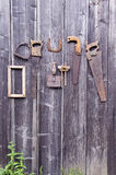 Antique handicraft tools and horseshoe hanging on old  wall Stock Photography