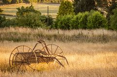 Antique hay rake in a farmers field at sunset. stock photography