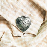 Antique heart shape ornament on check pattern cloth background. Top view Royalty Free Stock Image