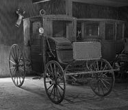 Antique horse-drawn carriages. Stored in a barn in black and white Royalty Free Stock Image