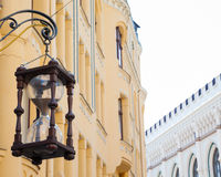 Antique hourglass hanging on building wall in old town of Royalty Free Stock Photos