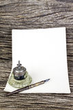 Antique  ink pen  and inkwell and old paper Royalty Free Stock Photos