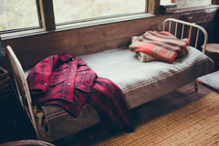 Antique  Iron Bed in Rustic Cabin With Plaid Coat Royalty Free Stock Images