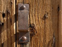 Antique iron handle on weathered door. Antique iron handle on old weathered door Stock Image