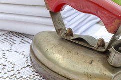 Antique iron with stack of linen clothes Stock Image