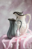 Antique Jugs. Two antique Victorian jugs on a table with pink ribbon and cloth Royalty Free Stock Photo