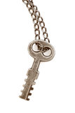 Antique key isolated. Very old and rusty key with original chain, on white background Stock Image