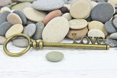Antique Key to Love on a beach stone background Stock Photography