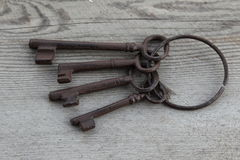 Old keys on weathered wood background. Antique keys on a weathered wood background Royalty Free Stock Image