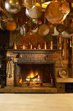 Antique kitchen with fireplace. And copper pans hanging Stock Image