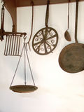Antique Kitchen Utensils. View of antique rusty kitchen utensils against a white wall stock photo