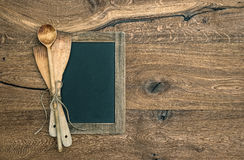 Antique kitchen utensils and blackboard on wooden background Stock Images