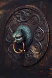 Antique knob on a wooden door, Augsburg, Germany. Antique knocker on a wooden door on facade of Cathedral of St. Maria (Dom Unserer Lieben Frau) in Augsburg Royalty Free Stock Photo