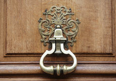 Antique knocker with pattern on wooden brown door, close up macro stuff concept Stock Photos
