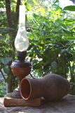 Antique lamp jug and an old book on the background of the garden. Antique lamp jug and an old book of the surface on the background of the garden Royalty Free Stock Image