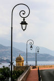 Antique lamp posts along a street with sea view in Monaco Royalty Free Stock Photography