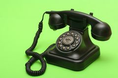 Antique landline phone. Antique black landline phone on green backdrop Stock Photography