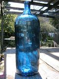Antique large blue apothecary bottle in natural sunlight. Antique large blue apothecary bottle. Photo taken outside mid summer. Photo taken with a Sony a3000 royalty free stock images