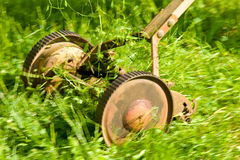 Antique lawn mower in action. Old, cast iron lawn mower in action Stock Image