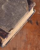 Antique leather bound book laying on an old rustic wood Royalty Free Stock Photo