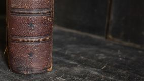 Antique leather bound book standing on an old wooden bookshelf. Antique leather bound book standing alone on an old wooden bookshelf Royalty Free Stock Image