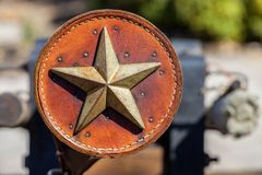 Antique leather ornament decorated with metal Texas star. Leather cover used on the barrel of an antique cannon stock image