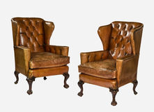Antique leather wing chair carved legs isolated with clip path. Pair old antique brown leather wing arm chair 18 - 19th century royalty free stock photos