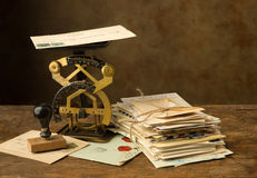 Antique letter scale and old letters. Antique letter scale on an old wooden table with a bundle of letters Royalty Free Stock Image