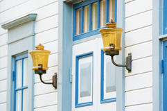 Antique lighting. Antique golden lighting with metal arms outside white and blue building, on either side of door. Seen from side with one light in focus and the stock photography