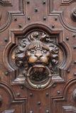 Antique Lion Head Door Knocker on Wooden Door. Found this in Brugge, Belgium. This lions head door knocker is carved into the intricately designed antique wooden Royalty Free Stock Image