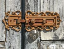 Antique lock and modern lock secure weathered doors. Double set of locks. The antique lock is supplemented with modern keyed entry lock on weathered doors stock photos