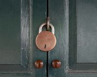 Antique locked with old rusted padlock on green door.