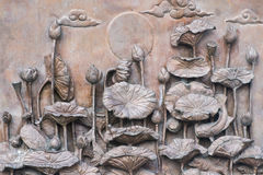 Antique lotus statue on the wall stock photo