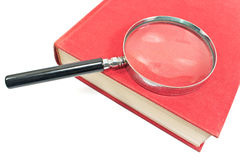 Antique magnifying glass on book Royalty Free Stock Photos