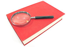 Antique magnifying glass on red book Stock Photos