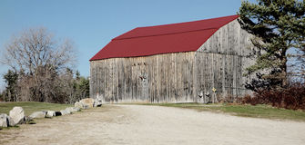Antique Maine barn barnyard. Old Maine barn and barnyard with stone border and winter trees Stock Photos