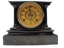 Antique mantle clock. A black and gold antique mantle clock with the minute hand about to strike 12 o-clock isolated on a white background Stock Photo