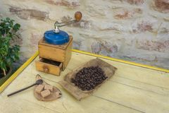 Vintage manual coffee grinder and coffee beans on old wooden table. Background - stone wall stock image