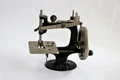 Antique manual hand crank sewing machine. On a white background. used for sewing doll cloths Royalty Free Stock Photo