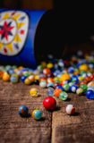 Antique Marble Collection. A collection of colorful antique glass marbles spilling out of an antique metal tin onto a wooden floor Stock Image