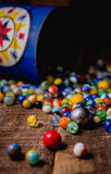Antique Marble Collection. A collection of colorful antique glass marbles spilling out of an antique metal tin onto a wooden floor Stock Photography