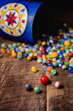 Antique Marble Collection. A collection of colorful antique glass marbles spilling out of an antique metal tin onto a wooden floor Royalty Free Stock Images